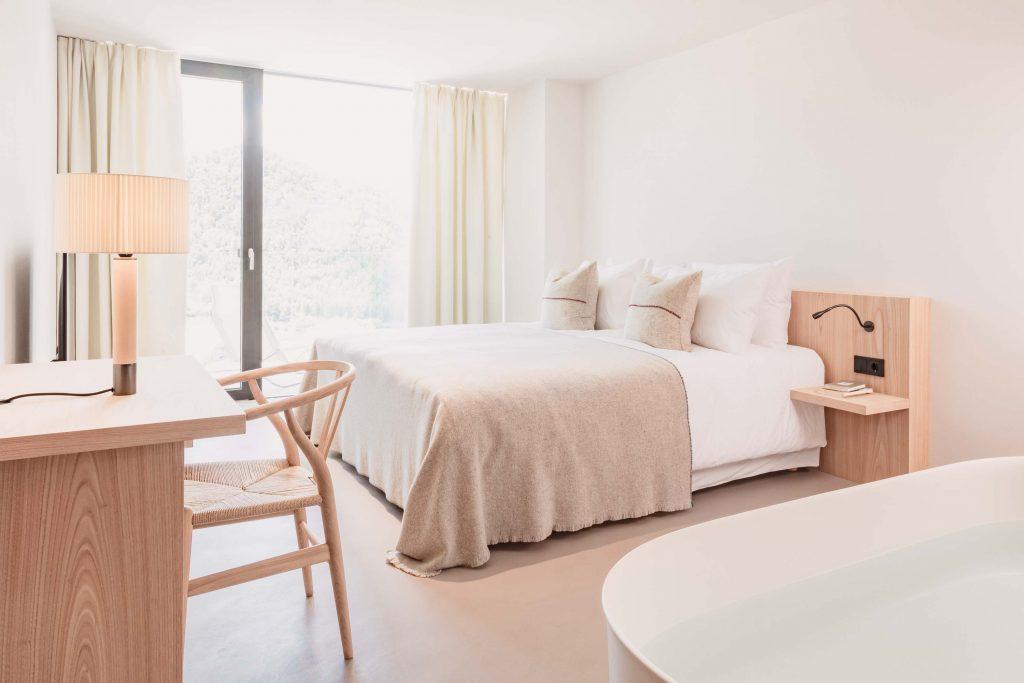 Hauptschlafzimmer der Familiensuite mit Schreibtisch, freistehender Badewanne und Bergblick