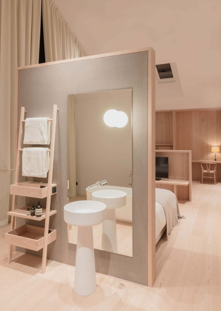 Die Townsuite des Hotel Schgaguler mit offenem Badezimmer, Wohnbereich und Blick auf den Kirchturm von Kastelruth